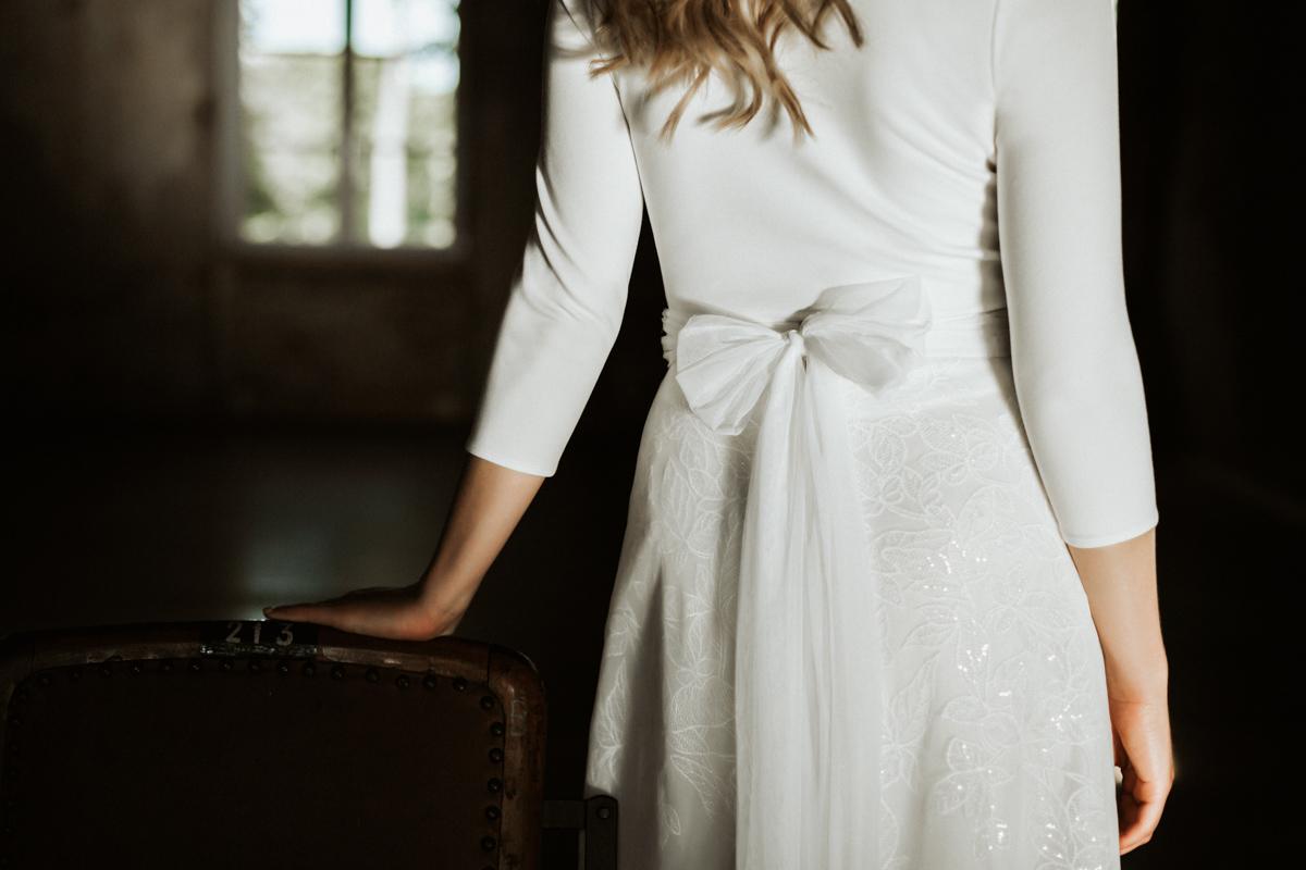 Querformat: Blonde Frau mit Top in Ivory, Schleifenschärpe und langem Rock mit Efeu-Muster, Nahaufnahme in Rückenansicht