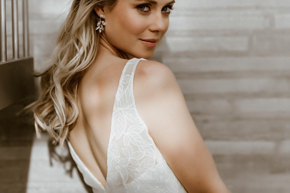 Querformat: Blonde Frau vor Steinwand in Brautkleid mit V-Ausschnitt und Efeu-Muster in Ivory