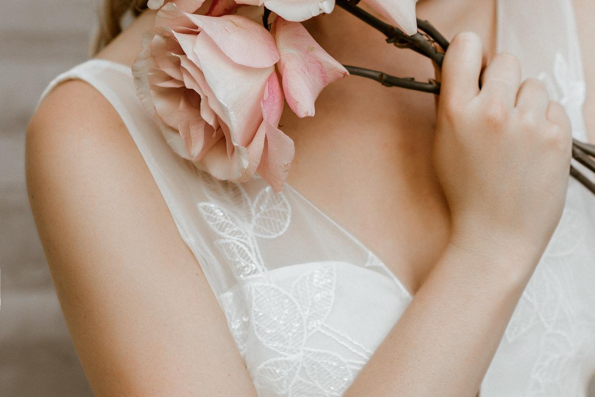 Querformat: Brautkleid mit V-Ausschnitt und Efeu-Muster in Ivory, Rosenstrauss haltend, Nahaufnahme von Ausschnitt
