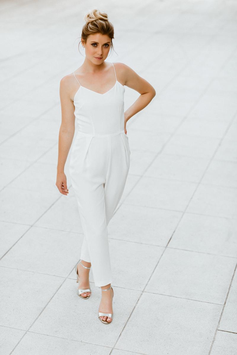 Hochformat: Blonde Frau mit Dutt, Ganzkörper-Aufnahme. Frau trägt weißen Brautjumpsuit und silberne Brautsandalen.