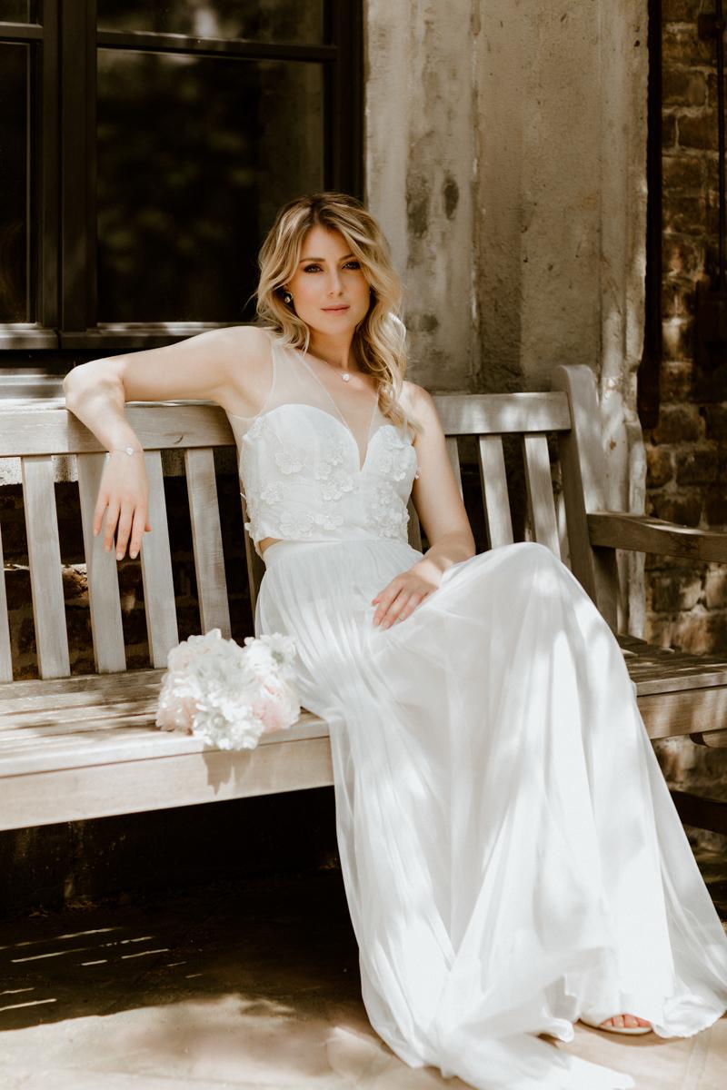 Hochformat: Blonde Frau mit ärmellosem Tülltop mit V-Ausschnitt und Blütenstickerei zu langem Tüllrock in Ivory, auf Bank in Sonne sitzend