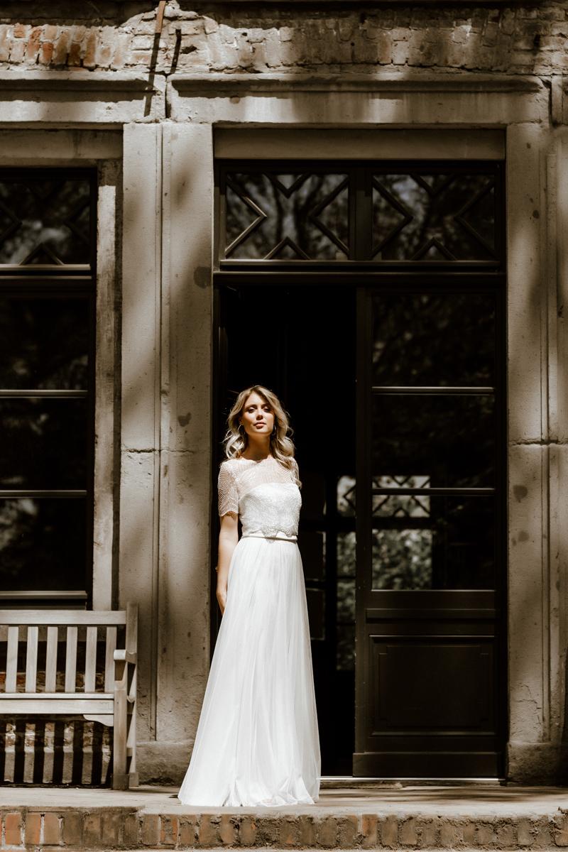 Hochformat: Blonde Frau mit Paillettentop und langem Tüllrock in Ivory