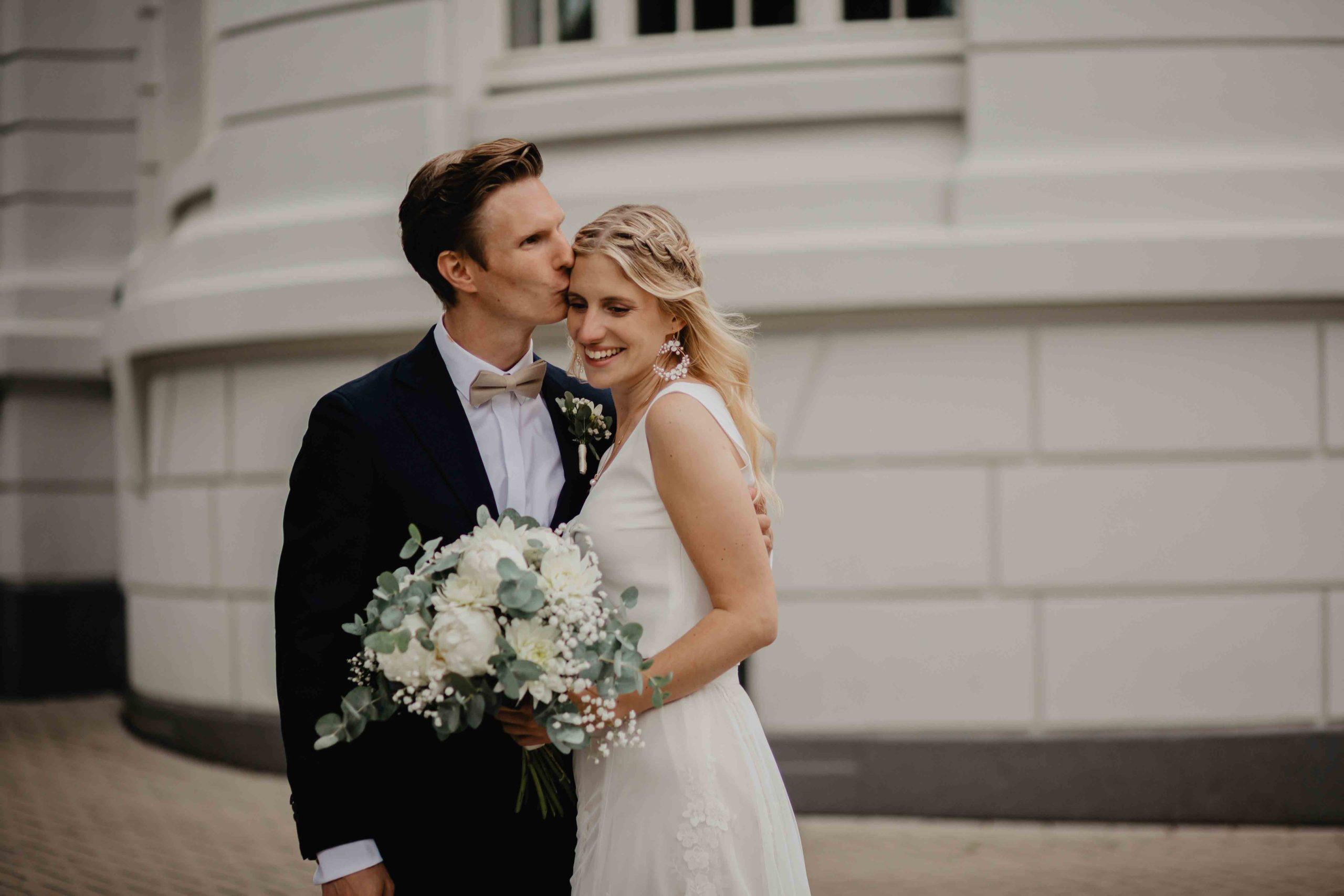 Bräutigam küsst Braut auf Wange