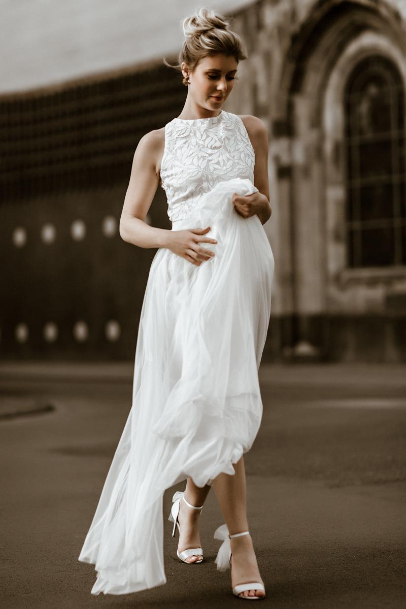 Hochformat: Blondes Modell mit Hochsteckfrisur, ärmellosem Top mit Blättermuster und langem weißen Tüllrock und weißen Brautsandaletten