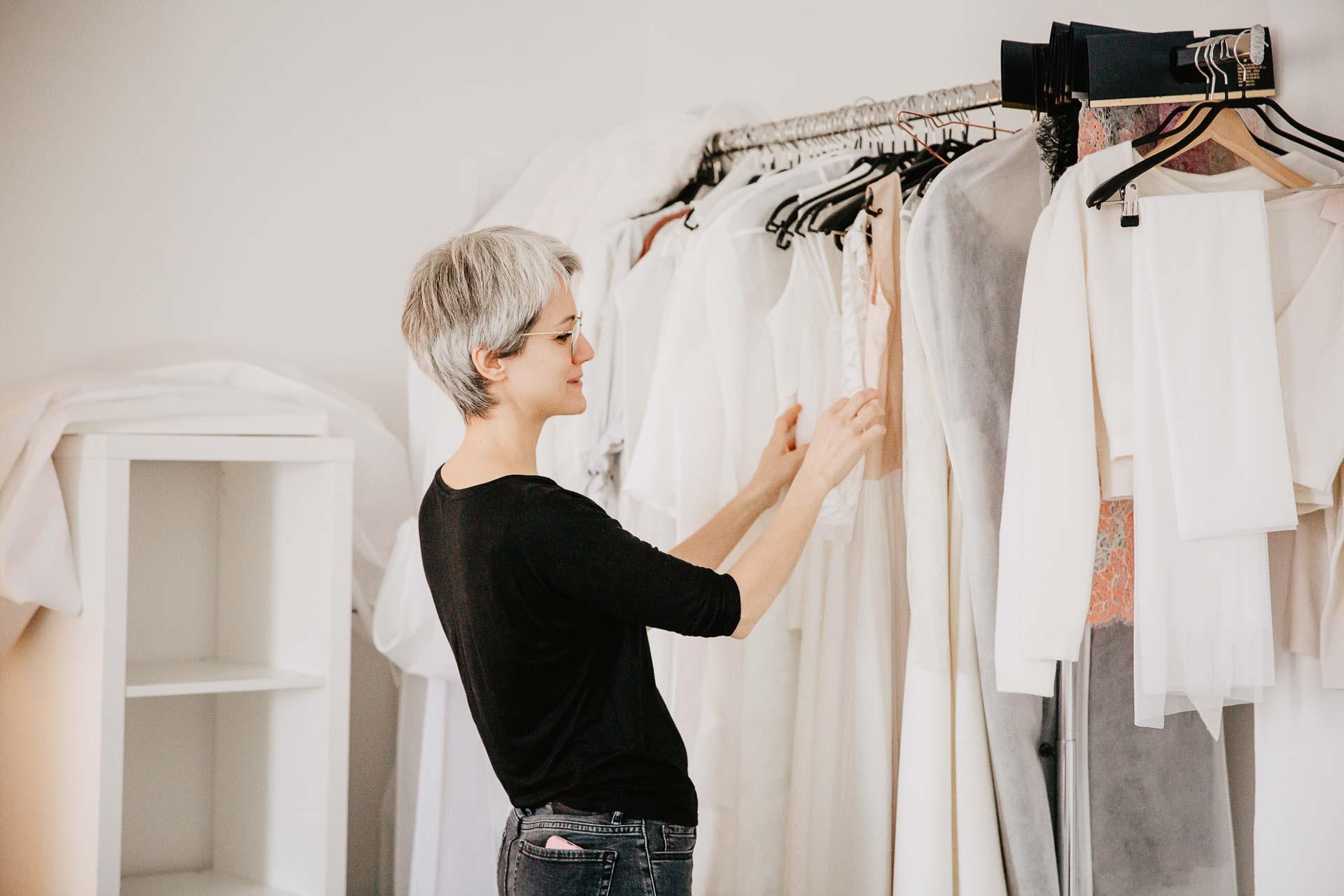 Frau an Kleiderstange mit Brautkleidern